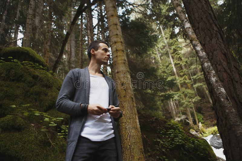 Young stylish man sitting on the precipice of the river on the phone stock images