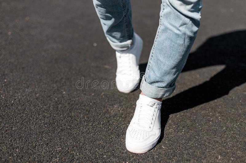 Young stylish man in leather white sneakers is walking along the road on a summer day. Male legs close-up. stock photography