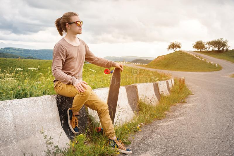 Young stylish man with long hair in sunglasses is sitting on a chipper with a longboard in his hands on a country. Asphalt road. On the background of rocks and stock photography