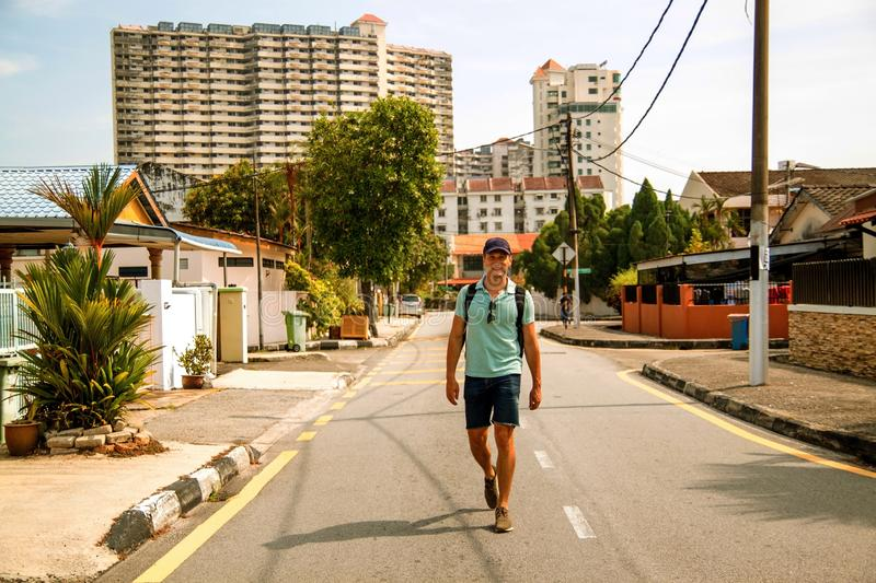 Young stylish man outdoors walking in the asian city . Happy young guy with backpack travels in asian city on sunny day stock image