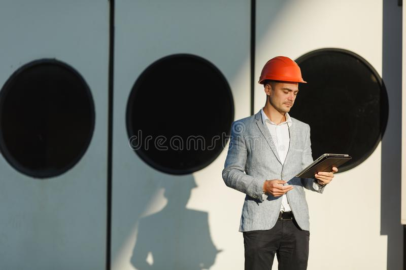 A young stylish man in a protective helmet against the backdrop of a seaport royalty free stock photography