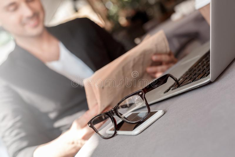 Lunch time. Young man in suit sitting at cafe on city street reading newspaper joyful blurred eyeglasses and phone close stock photography