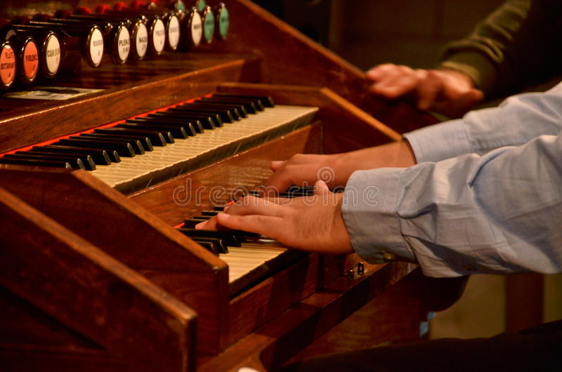 Young stylish musician is playing old organs in church in France. Conductor conducts his choir by playing the organ stock photo