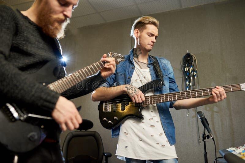 Creative men playing guitars in studio royalty free stock photo