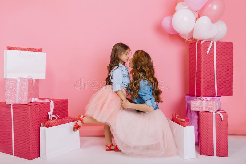 Young stylish pretty woman congratulates daughter in lush skirt on birthday holding her by the hands on pink background stock photos