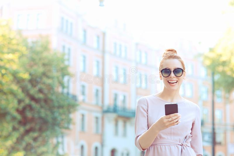 Young stylish pretty woman using smart phone walking on the street royalty free stock photo