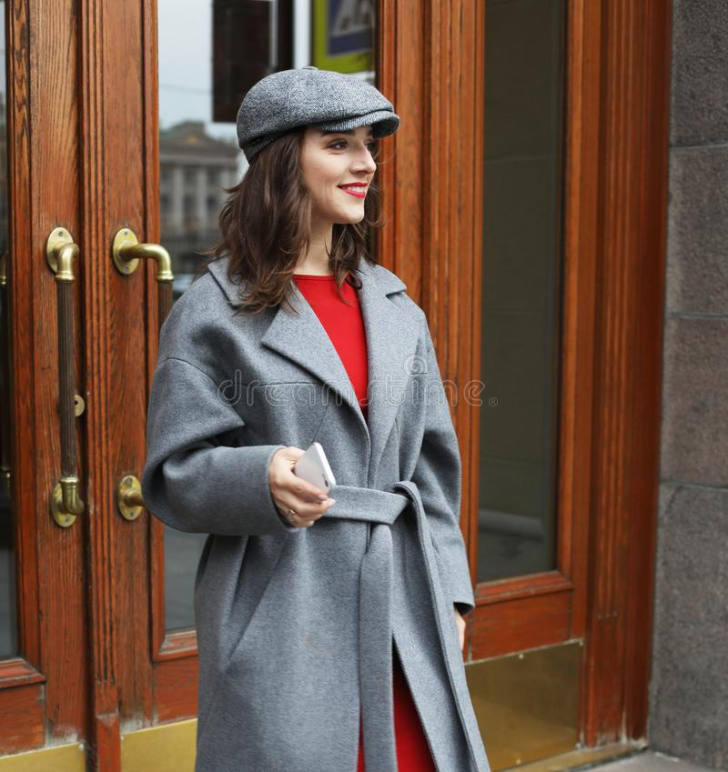Young stylish pretty woman wearing red dress, grey coat and hat posing in the city streets. royalty free stock photography