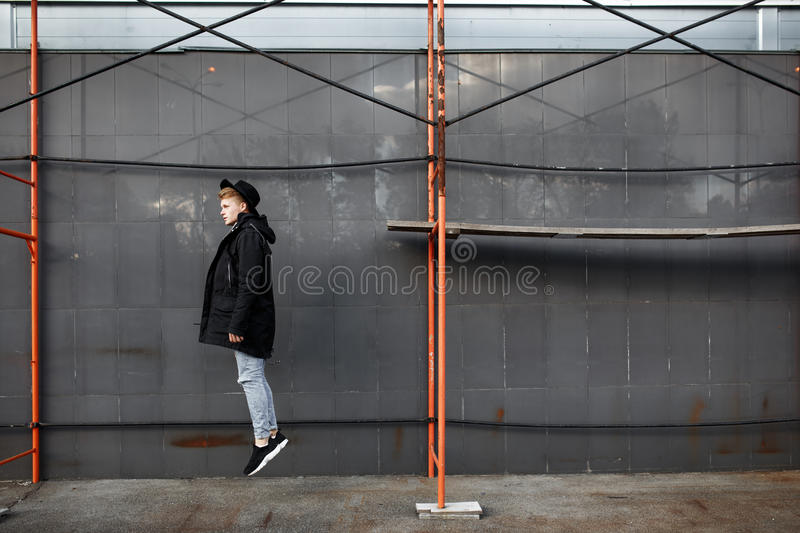 Young stylish redhead man in trendy outfit have fun and jumping against urban wall outdoors. stock photography