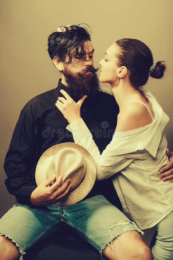 Young stylish sexy couple with hat. Young sexy couple of women with glamour makeup on pretty face in stylish shirt and bra kiss handsome bearded men with long stock photography