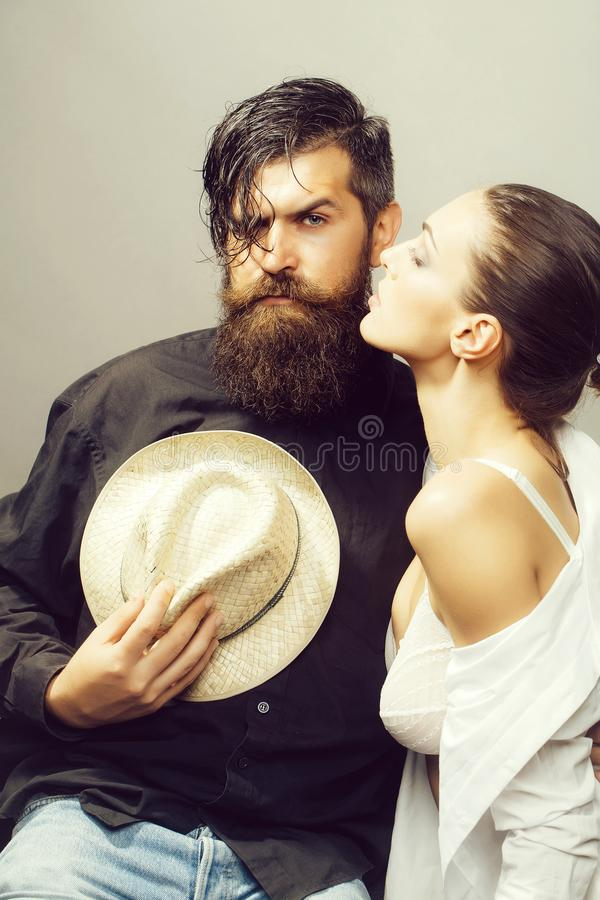 Young stylish sexy couple with hat. Young sexy couple of women with glamour makeup on pretty face in stylish shirt and bra kiss handsome bearded men with long royalty free stock images