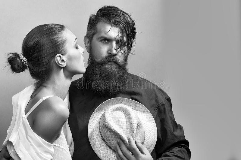 Young stylish couple with hat. Young couple of women with glamour makeup on pretty face in stylish shirt and bra kiss handsome bearded men with long beard and stock image
