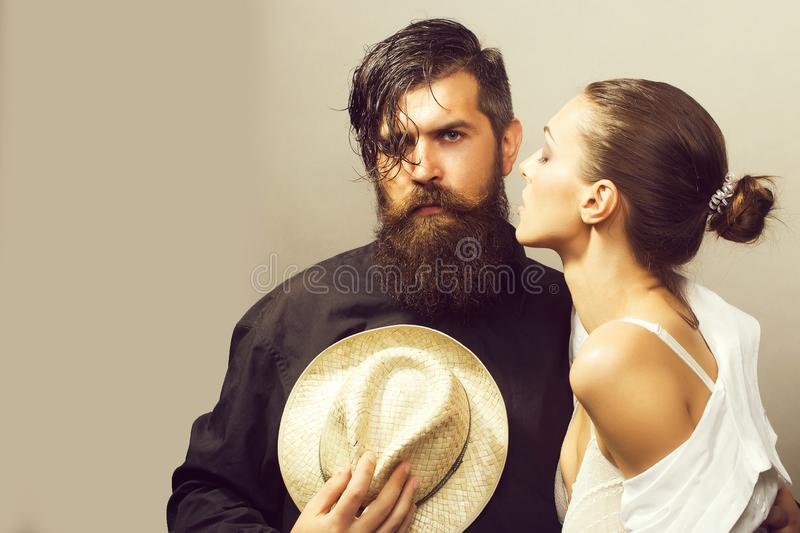 Young stylish couple with hat. Young couple of women with glamour makeup on pretty face in stylish shirt and bra kiss handsome bearded men with long beard and stock images