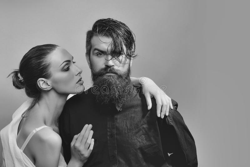 Young stylish couple in studio. Couple of women with glamour makeup on pretty face in stylish shirt and bra near handsome bearded men with long beard and wet royalty free stock images