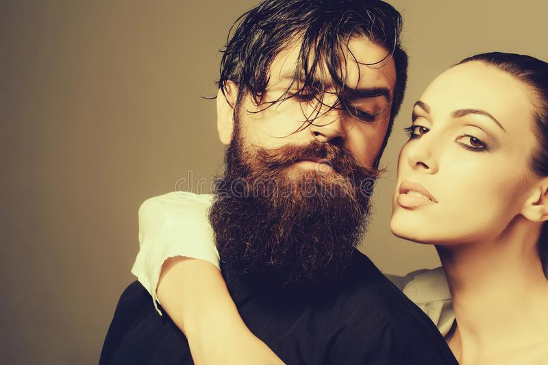 Young stylish couple in studio. Young couple of women with glamour makeup on pretty face in stylish shirt and bra near handsome bearded men with long beard and royalty free stock photography