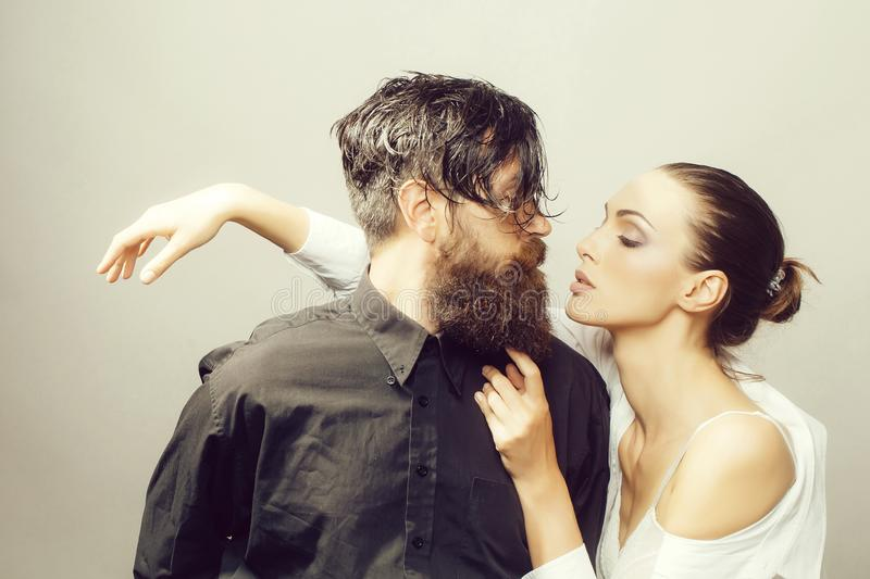 Young stylish couple in studio. Young couple of women with glamour makeup on pretty face in stylish shirt and bra near handsome bearded men with long beard and stock images