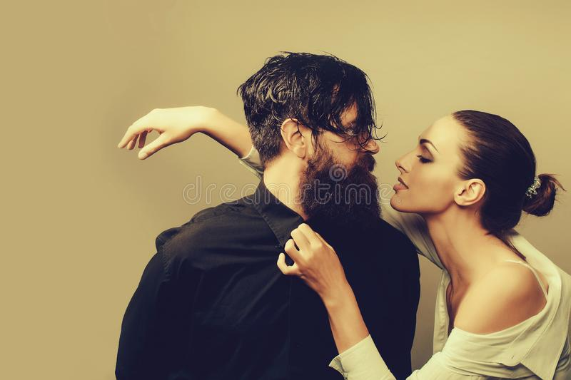 Young stylish couple in studio. Young couple of women with glamour makeup on pretty face in stylish shirt and bra near handsome bearded men with long beard and stock photo