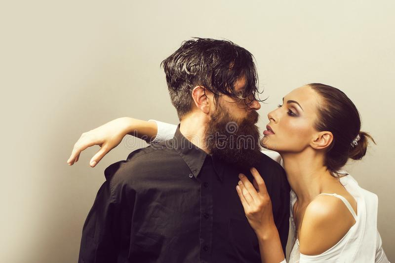 Young stylish sexy couple in studio. Young sexy couple of women with glamour makeup on pretty face in stylish shirt and bra near handsome bearded men with long royalty free stock images