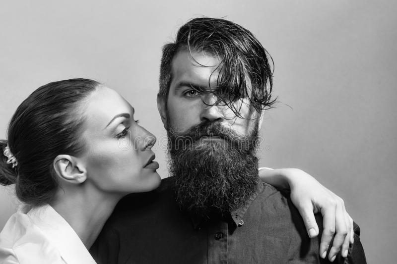 Young stylish couple in studio. Young couple of women with glamour makeup on pretty face in stylish shirt and bra near handsome bearded men with long beard and royalty free stock photos
