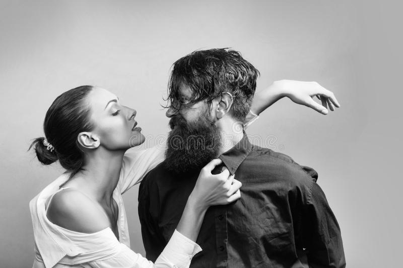 Young stylish couple in studio. Young couple of women with glamour makeup on pretty face in stylish shirt and bra near handsome bearded men with long beard and stock photography