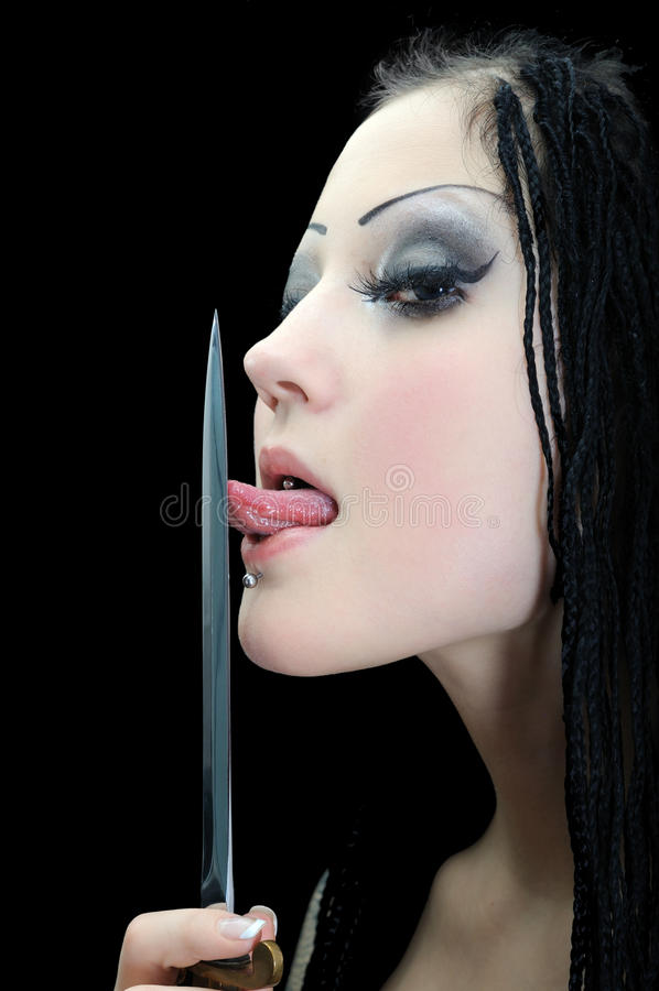Young stylish woman with dreadlocks, licking a dagger royalty free stock images