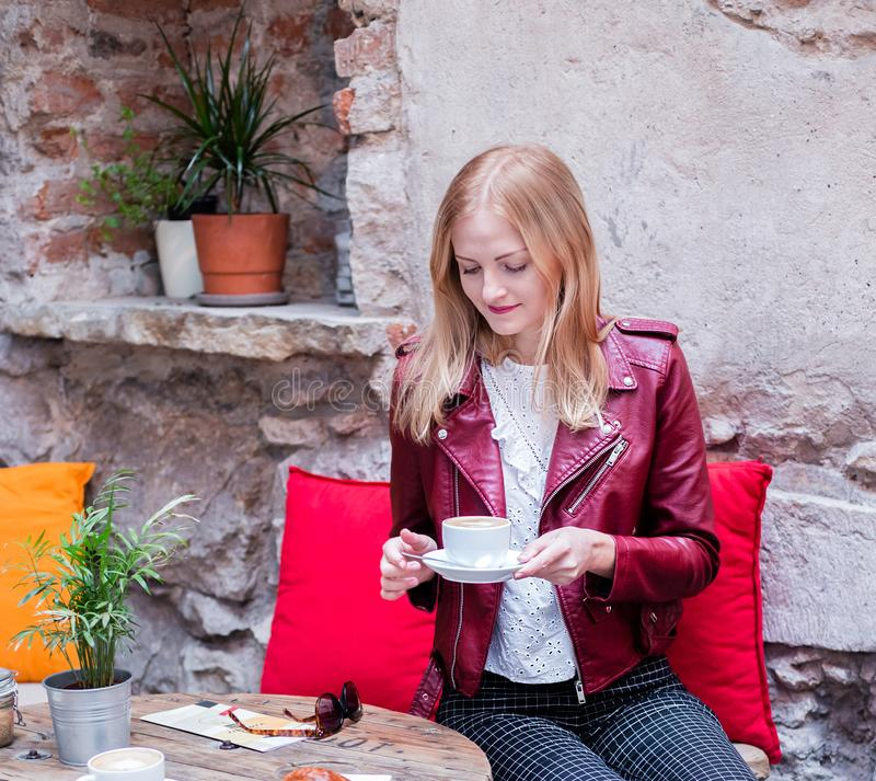 Young stylish woman with coffee and croissant sitting oudoors at the cafe terrace royalty free stock photo