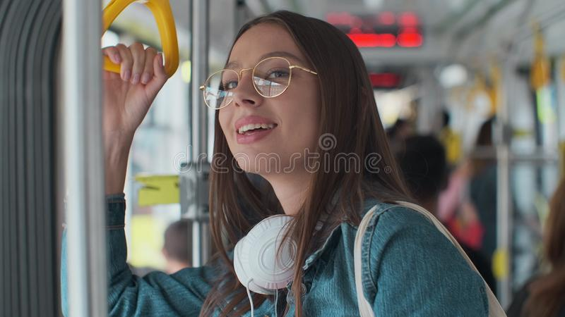 Young stylish woman enjoying trip in the modern tram, standing with coffee in the public transport. Young stylish woman enjoying trip in the modern tram stock photo