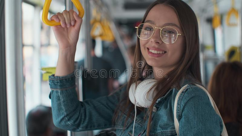 Young stylish woman enjoying trip in the modern tram, standing with coffee in the public transport.  stock photo