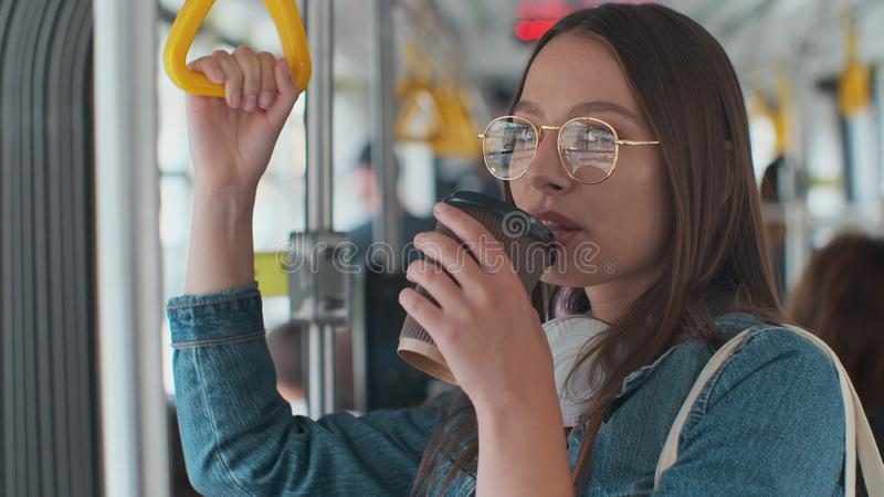 Young stylish woman enjoying trip in the modern tram, standing with coffee in the public transport. Young stylish woman enjoying trip in the modern tram royalty free stock photos