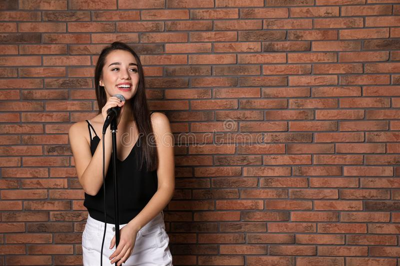Young stylish woman posing with microphone near brick wall. Space for text stock photo