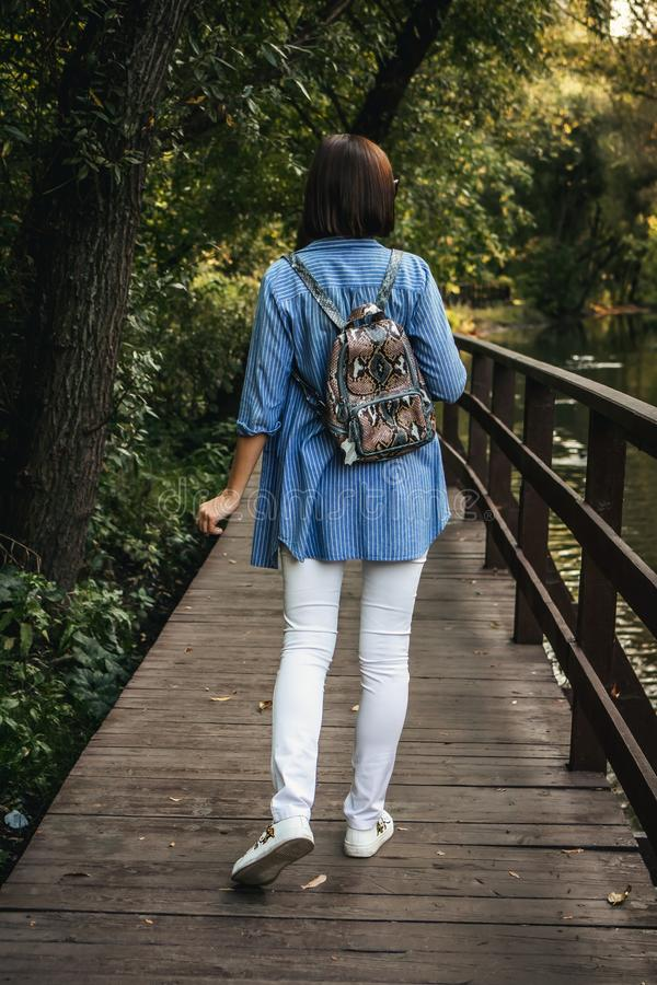 Young stylish woman with snakeskin python backpack. royalty free stock photography