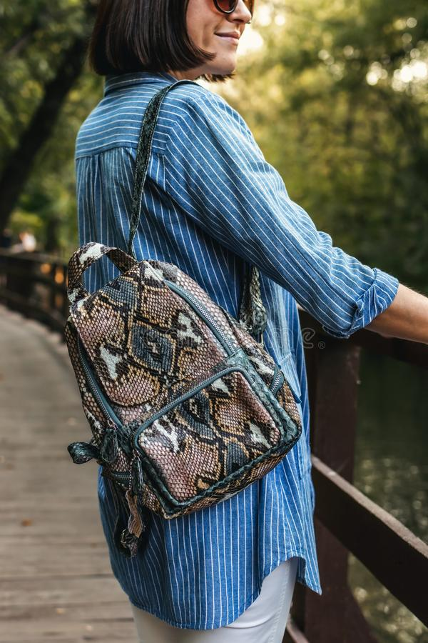 Young stylish woman with snakeskin python backpack. royalty free stock images