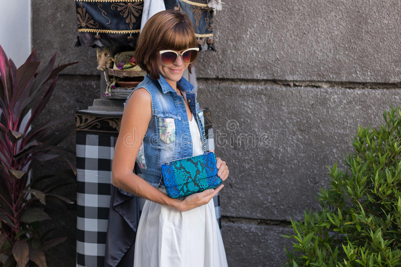 Young stylish woman in trendy outfit with snakeskin python luxury bag in hands. Woman with handbag near the swimming stock image