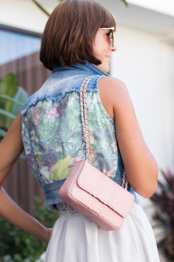 Young stylish woman in trendy outfit with snakeskin python luxury bag in hands. Woman with handbag near the swimming stock photography