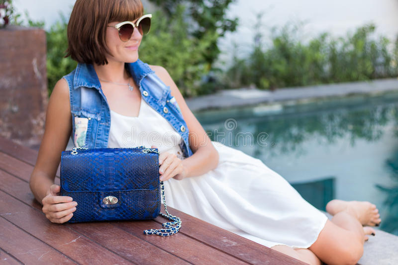 Young stylish woman in trendy outfit with snakeskin python luxury bag in hands. Woman with handbag near the swimming. Young stylish woman in trendy outfit with royalty free stock photos