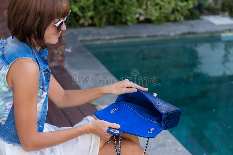 Young stylish woman in trendy outfit with snakeskin python luxury bag in hands. Woman with handbag near the swimming. Young stylish woman in trendy outfit with stock images