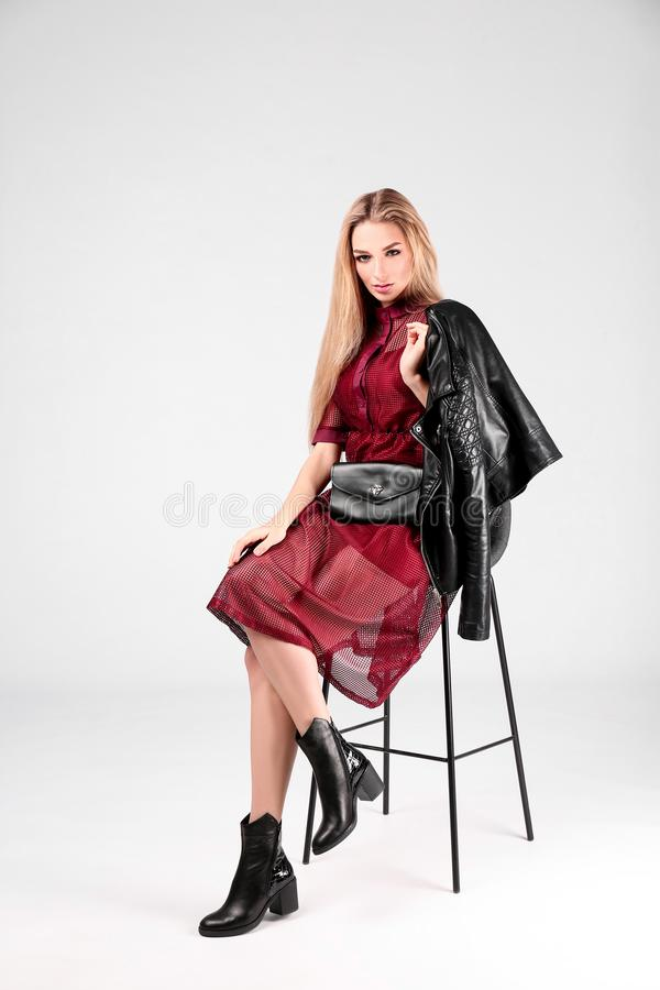 Young stylish woman in trendy shoes with bum bag sitting on bar stool. Light background stock images