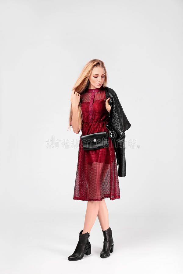 Young stylish woman in trendy shoes with bum bag. On light background royalty free stock photo