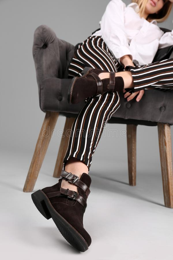 Young stylish woman with trendy shoes sitting in armchair on grey. Background stock photography