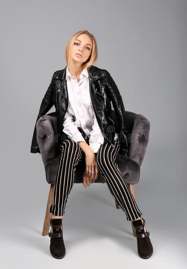 Young stylish woman with trendy shoes sitting in armchair. On grey background stock images