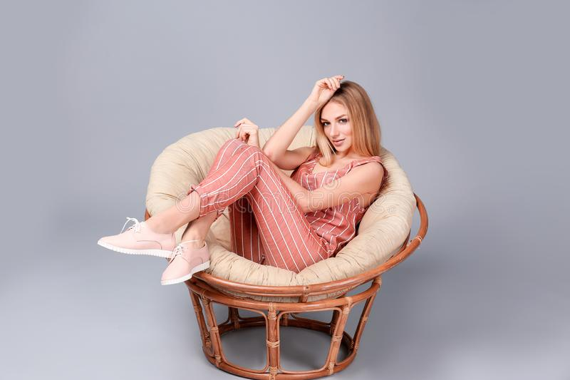 Young stylish woman with trendy shoes sitting in papasan chair. On grey background stock photo