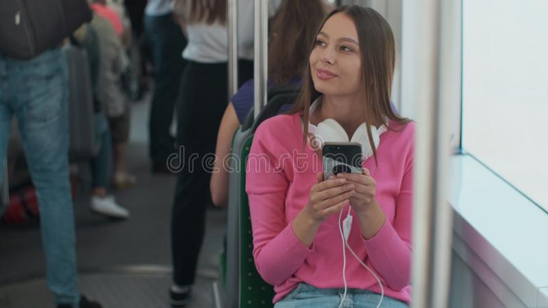 Young stylish woman using public transport, sitting with phone and headphones in the modern tram. Young stylish woman using public transport, sitting with phone stock photos