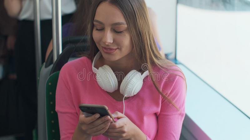 Young stylish woman using public transport, sitting with phone and headphones in the modern tram. Young stylish woman using public transport, sitting with phone stock photo