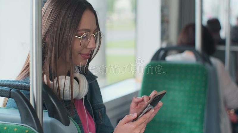 Young stylish woman using public transport, sitting with phone and headphones in the modern tram. Young stylish woman using public transport, sitting with phone royalty free stock photo