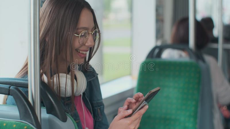 Young stylish woman using public transport, sitting with phone and headphones in the modern tram. Young stylish woman using public transport, sitting with phone stock images