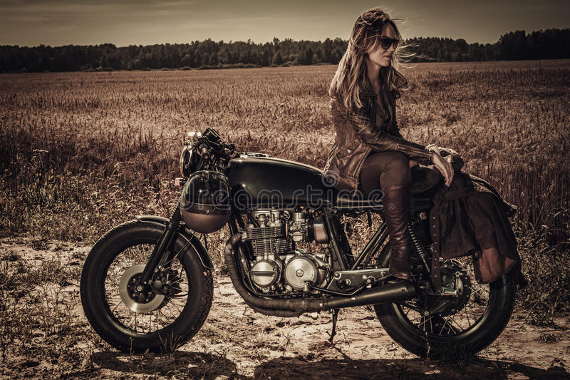 Young, stylish woman on vintage custom cafe racer in field.  stock photo