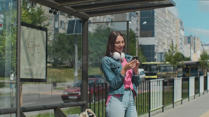 Young stylish woman waiting for the public transport while standing at the modern tram station outdoors. royalty free stock images