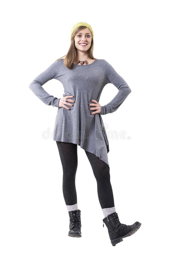 Young stylish woman wearing tights, boots, gray tunic and yellow beanie cap smiling. royalty free stock photography