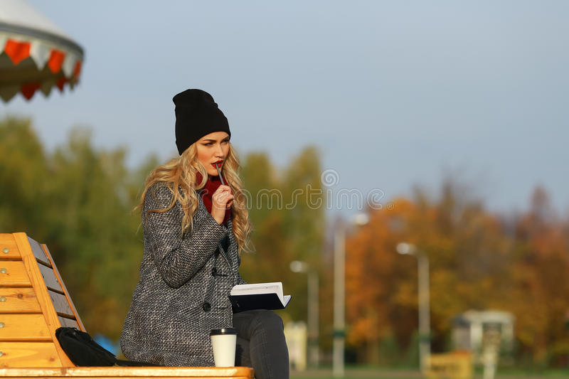 Young stylish woman working in a park with her pen in her mouth stock image