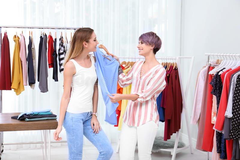 Young stylist helping customer to choose clothes stock photos