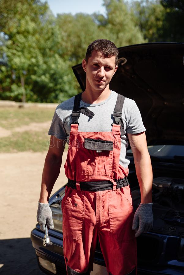 Young succesful professional car repairman in flannel and overalls standing by automobile under repair royalty free stock photo